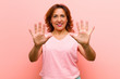 canvas print picture - middle age woman smiling and looking friendly, showing number ten or tenth with hand forward, counting down against pink wall