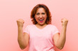canvas print picture - middle age woman feeling happy, surprised and proud, shouting and celebrating success with a big smile against pink wall