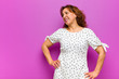 Leinwanddruck Bild - middle age woman looking happy, cheerful and confident, smiling proudly and looking to side with both hands on hips against purple wall