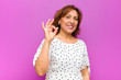 canvas print picture middle age woman feeling happy, relaxed and satisfied, showing approval with okay gesture, smiling against purple wall