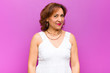 Leinwanddruck Bild - middle age woman looking proud, confident, cool, cheeky and arrogant, smiling, feeling successful against purple wall