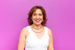 canvas print picture - middle age woman looking happy and goofy with a broad, fun, loony smile and eyes wide open against purple wall