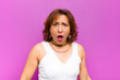 canvas print picture - middle age woman looking shocked, angry, annoyed or disappointed, open mouthed and furious against purple wall