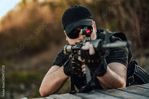 Fotografie, Obraz Close-up image of man aiming with sniper rifle.