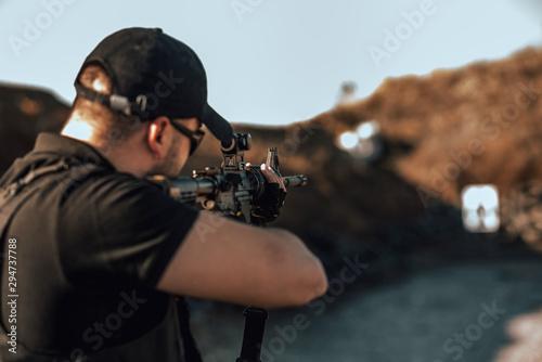 Close-up image of armed guy shooting at target outdoors. Fototapeta