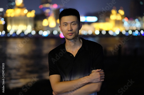 Fotografia one handsome asian young man standing at the Bund in Shanghai at night