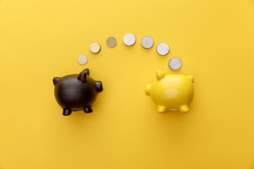 top view of piggy banks with coins on yellow background