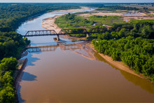 Aerial Photo Of Train Trestle Crossing Muddy River That Winds Into The Landscape On The Texas And Oklahoma Border | Train Tracks Crossing River