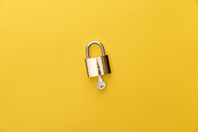 Top View Of Key In Padlock On Yellow Background