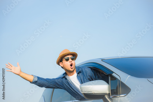 Fototapeta  Young handsome asian man driving car to travel on his holiday vacation time with beautiful blue sky