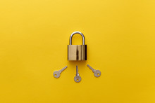 Top View Of Metal Padlock With Keys On Yellow Background