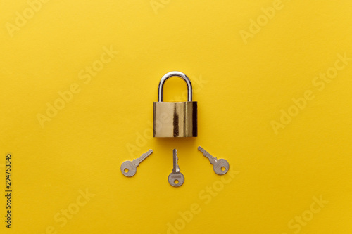Cuadros en Lienzo  top view of metal padlock with keys on yellow background