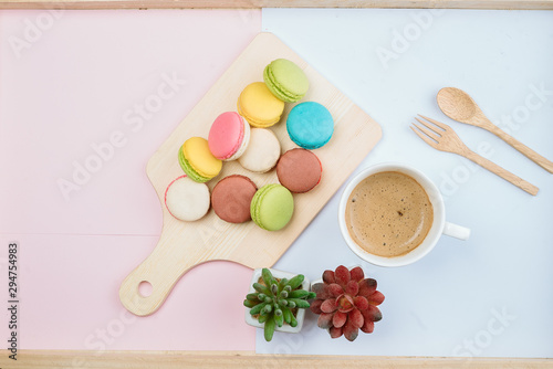 Delicious and colorful macarons placed on a wooden tree decorated with sweet coffee.