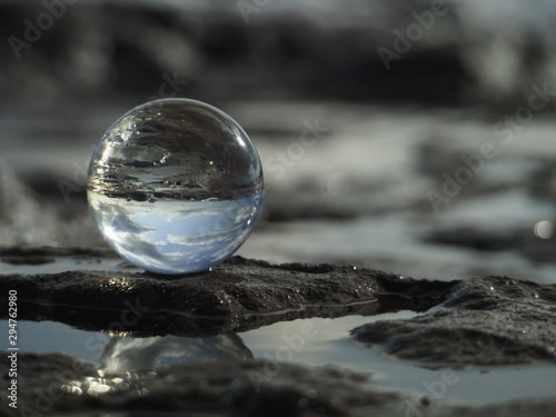 Fotografía  Close shot of a glass sphere reflecting the water in the middle of the rocks und