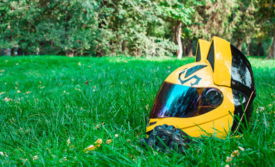 A yellow biker girl helmet from a motorcycle with mirror glass and ears and black biker gloves lies on green grass against the background of a gray motorcycle in autumn.