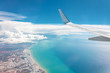 canvas print picture Blue sky high wing view of the sea coast from an airplane, far away white clouds.