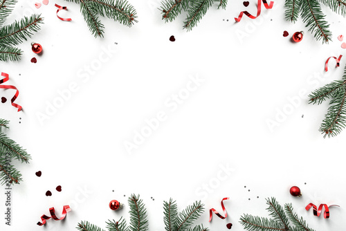 Fotografía  Creative frame made of Christmas fir branches on white background with red decoration, pine cones