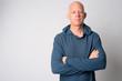 Leinwanddruck Bild - Portrait of mature handsome bald man with arms crossed