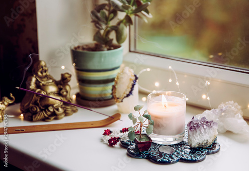 Feng Shui altar at home in living room or bed room. Attracting wealth and prosperity concept. Crystal clusters, wire tree with gemstones, golden smiling Buddha figure on table window sill.
