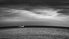 Greyscale Shot Of A Ship In The Ocean Under The Crazy Cloudy Sky