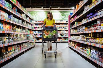 kobieta z zakupami między półką sklepową