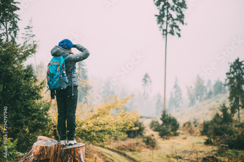 Fotomural  Young Woman Standing On Stump In Forest And Looking Into Distance In Deforestation Zone