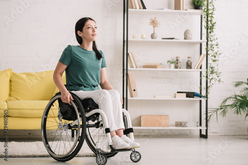 Obraz smiling disabled woman looking away while sitting in wheelchair at home - fototapety do salonu