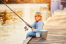 A Little Girl Fishing With A Fishing Rod From A Pontoon Or Pier On The Pond Fish Farm
