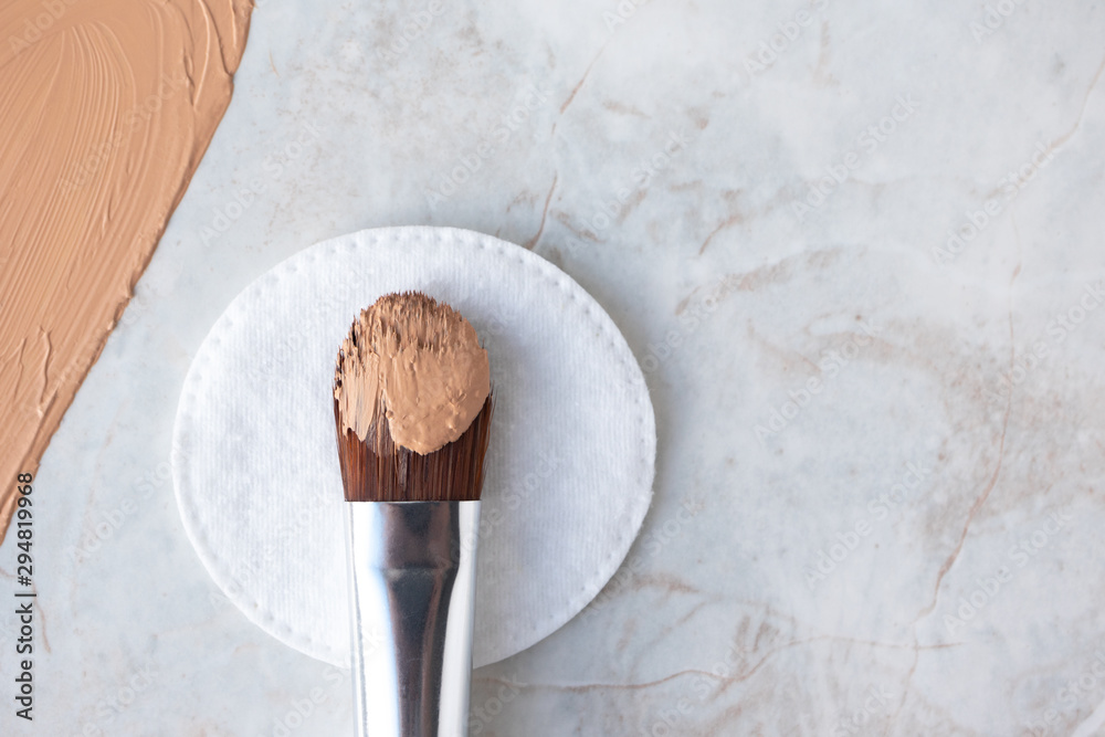 Fototapeta Make up brush with BB cream, CC cream or foundation on white cotton round and luxury marble background, top view. Daily makeup