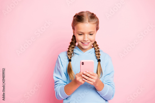 Obraz Photo of pretty little lady holding telephone hands reading positive comments for new post wear casual blue hoodie pullover isolated pastel pink color background - fototapety do salonu