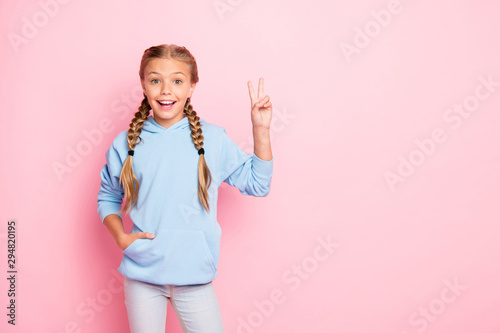 Obraz Hi you. What's up. Photo of pretty small lady raising hand showing v-sign symbol greets school friends wear casual blue pullover isolated pastel pink color background - fototapety do salonu