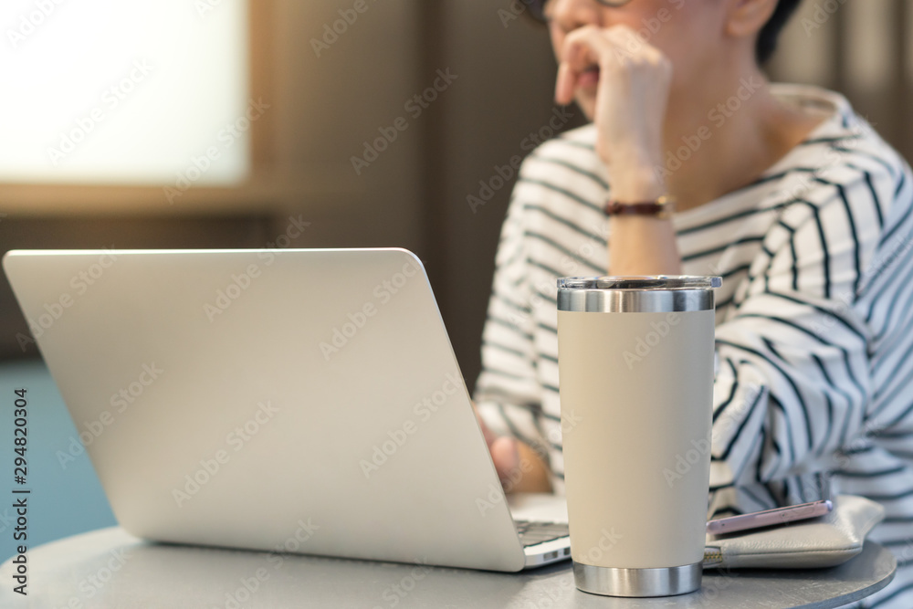 Fototapeta Smart looking woman use laptop computer to work from home due to Covid-19 pandemic, city lockdown and social distancing with her drink in a reusable stainless steel tumbler mug aside.