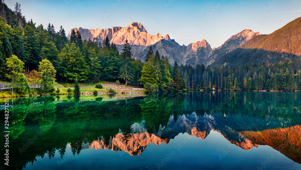 Fototapeta Calm morning view of Fusine lake. Colorful summer sunrise in Julian Alps with Mangart peak on background, Province of Udine, Italy, Europe. Beauty of nature concept background.