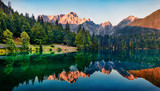 Fototapeta Natura - Calm morning view of Fusine lake. Colorful summer sunrise in Julian Alps with Mangart peak on background, Province of Udine, Italy, Europe. Beauty of nature concept background.