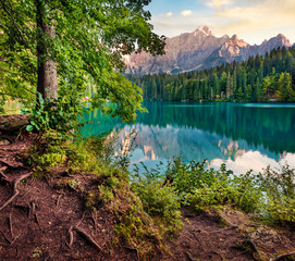 Fototapeta Krajobraz Sunny morning view of Fusine lake. Colorful summer sunrise in Julian Alps with Mangart peak on background, Province of Udine, Italy, Europe. Traveling concept background.
