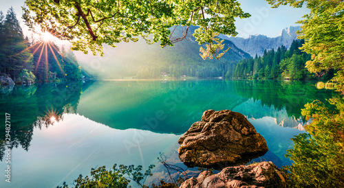 Impressive morning view of Fusine lake. Attractive summer scene of Julian Alps with Mangart peak on background, Province of Udine, Italy, Europe. Traveling concept background.