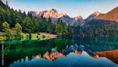 Obraz Calm morning view of Fusine lake. Colorful summer sunrise in Julian Alps with Mangart peak on background, Province of Udine, Italy, Europe. Beauty of nature concept background. - fototapety do salonu