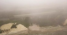 Aerial View Of An Abandoned Bridge And Traffic On The Highway Behind. Drone Descending Shot View Trhought Smog, Apocalyptic Scenery