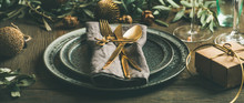 Christmas Or New Years Celebration Party Table Setting. Plates, Golden Cutlery, Glasses, Gift Box, Festive Branch Decoration, Candles, Gliterring Toys Over Rustic Wooden Table Background