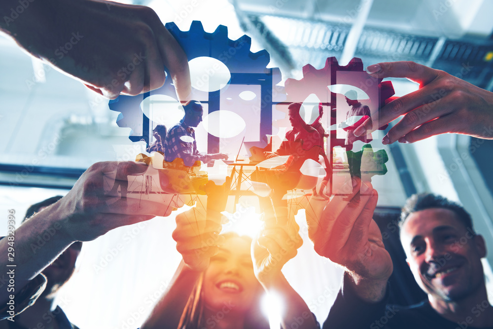 Fototapeta Business team connect pieces of gears. Teamwork, partnership and integration concept. double exposure with light effects