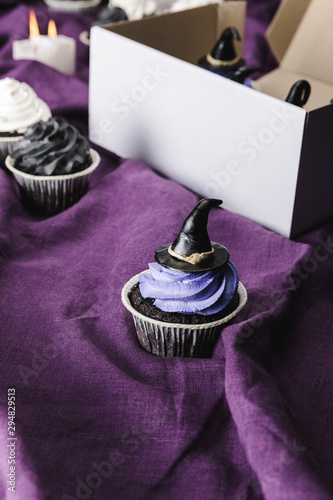 tasty Halloween cupcake with blue cream and decorative witch hat on purple cloth