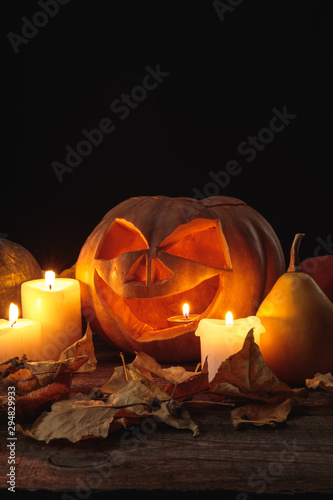 Obraz dry foliage, burning candles and Halloween carved pumpkin on wooden rustic table isolated on black - fototapety do salonu