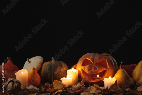dry foliage, burning candles and Halloween carved pumpkin on wooden rustic table isolated on black