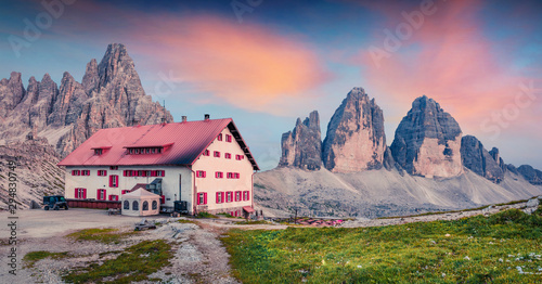 Fotobehang Bleke violet Impressive summer sunset with Paternkofel and Tre Cime Di Lavaredo mpountain peaks. Fantastic summer scene of rifugio Locatelli in Dolomiti Alps , South Tyrol, Italy, Europe.