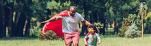 Panoramic Shot Of African American Father And Son Running In Costumes Of Superheroes In Park