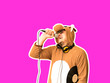 canvas print picture - Man in cosplay costume of a cow singing karaoke isolated on purple background. Guy in the funny animal pyjamas sleepwear holding microphone. Funny photo. Party ideas. Disco music.