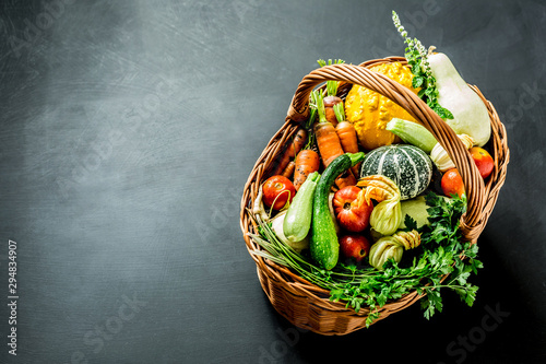 Canvastavla Colorful organic vegetables in wicker basket on black