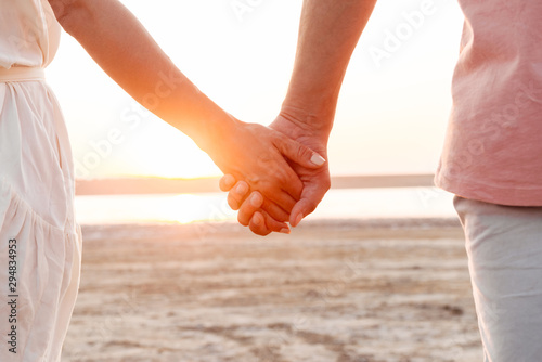 Fototapeta Close up of a couple holding hands at the beach obraz