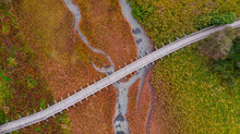 Wooden Bridge Over Autumnal Grassland. Abstract Pattern. Top Down Drone View