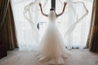Modern bridal style. Caucasian bride standing near the window in a hotel room.